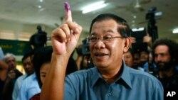 Thủ tướng Campuchia Hun Sen giơ ngón tay có dấu mực sau khi bỏ phiếu tại thành phố Takhmau, phía nam thủ đô Phnom Penh, ngày 28/7/2013.