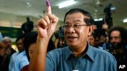 PM Kamboja Hun Sen menunjukkan jarinya setelah memberikan suara di TPS kota Takhmau, selatan ibukota Phnom Penh (28/7).