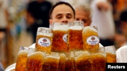 FILE - German Oliver Struempfl competes to set a new world record in carrying one liter beer mugs over a distance of 40 m (131 ft 3 in) in Abensberg, Sept. 7, 2014.