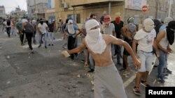 Para demonstran Palestina melemparkan batu ke arah pasukan keamanan Israel dalam protes di Shuafat, Yerusalem (5/10).