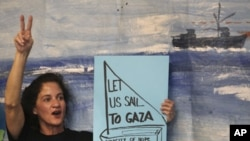 An activist holds a placard during a news conference regarding preparations of a flotilla, which is due to set sail to Gaza from Greece, in Athens, June 27, 2011