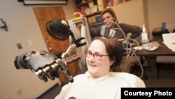 "Jan Scheuermann, who has quadriplegia, brings a chocolate bar to her mouth using a robot arm she is guiding with her thoughts. Researcher Elke Brown, M.D., watches in the background, Photo credit: ""UPMC"""