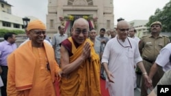 Tibetan spiritual leader the Dalai Lama, center, gestures as he leaves after attending an all faith prayer service for world peace and harmony organized by the Ramakrishna Mission in New Delhi, India, Tuesday, Sept. 11, 2012. (AP Photo/Altaf Qadri)