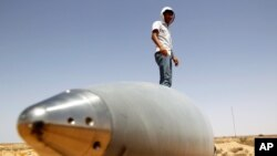 An anti-Gaddafi fighter stands on an SA-5 SAM missile in Burkan air defense military base, which was destroyed by a NATO air strike in August, 2011.