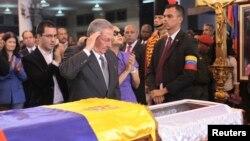 El presidente cubano Raúl Castro saluda frente a los restos de Chávez en Caracas. Los médicos cubanos que le atendieron serán condecorados.
