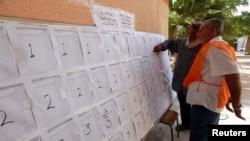 2014年6月25日,首都的黎波里一位官员协助选民校内投票前寻找自己的名字