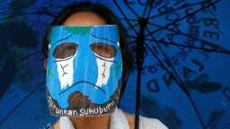 "Seorang remaja perempuan mengenakan faceshield bergambar ""Bumi yang menangis"" ikut serta dalam aksi protes mengenai iklim di luar Monumen Nasional (Monas) di Jakarta, 27 November 2020. (Photo: REUTERS/Willy Kurniawan)"