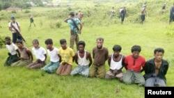 FILE - Ten Rohingya Muslim men with their hands bound kneel as members of the Myanmar security forces stand guard in Inn Din village, Sept. 2, 2017.