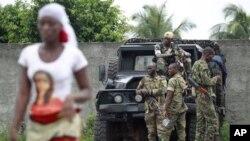 Une femme passant devant des soldats pro-Ouatarra, à Abidjan