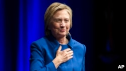 Hillary Clinton places her hand over her heart as she walks to the podium to address the Children's Defense Fund's Beat the Odds celebration at the Newseum in Washington, Nov. 16, 2016.
