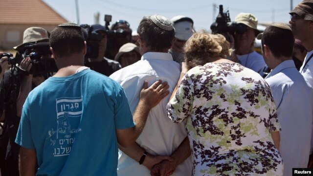 Jewish settlers speak to the media after leaving their homes in the West Bank outpost of Migron September 2, 2012.