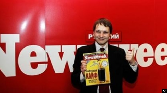 Editorial Director of Russian Newsweek Leonid Bershidsky gives a thumbs up while holding the first issue in Moscow 07 June 2004