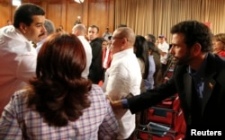 Venezuela's President Nicolas Maduro (L) shakes hands with opposition leader and governor of Miranda state Henrique Capriles during a meeting with mayors and governors at Miraflores Palace in Caracas, Jan. 8, 2014.