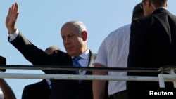 以色列总理内塔尼亚胡在特拉维夫登机到美之前向欢送的人士挥手致谢。