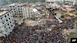 FILE - In this April 25, 2013, photo, people gather as rescuers look for survivors and victims at the site of a building that collapsed a day earlier, in Savar, near Dhaka, Bangladesh. The building housed five garment factories.
