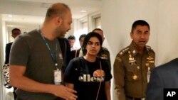 El jefe de la Policía de Inmigración, mayor general Surachate Hakparn, camina con la joven saudí Rahaf Mohammed Alqunun antes de salir del aeropuerto de Suvarnabhumi en Bangkok, Tailandia, el 7 de enero de 2019.