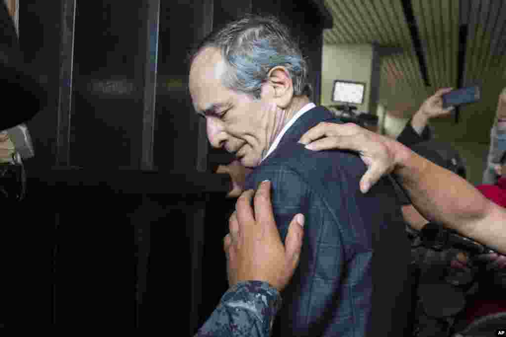 Police officers pat down former Guatemalan President Alvaro Colom before escorting him into a courthouse in Guatemala City. Colom, who governed from 2008 to 2012, has been detained in a corruption case, according to special prosecutor Juan Francisco Sandoval.