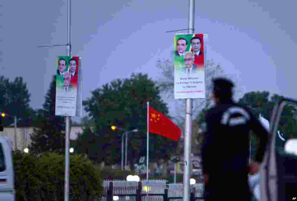A police officer stands guard next to billboards welcoming Chinese premier Li Keqiang hung on poles near the presidency in Islamabad, Pakistan.