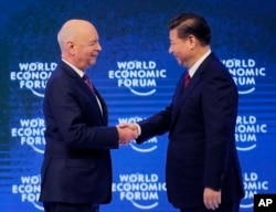China's President Xi Jinping, right, is welcomed by World Economic Forum founder Klaus Schwab.