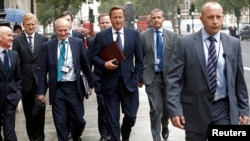 Britain's Prime Minister David Cameron (C) walks to Parliament after leaving Number 10 Downing Street in London Sep. 1, 2014.