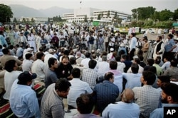 FILE - Pakistani journalists hold a protest rally and sit-in-protest outside the Parliament to condemn the killing of their colleague, Syed Salim Shahzad, this week after he reported being threatened by intelligence agents, in Islamabad, Pakistan, June 15, 2011.