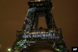 "FILE- Artwork entitled ""One Heart One Tree"" by artist Naziha Mestaoui is displayed on the Eiffel tower ahead of the 2015 Paris Climate Conference, in Paris, Nov. 29, 2015."