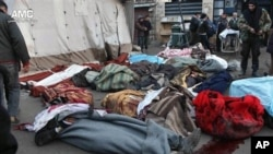 Syrians stand near the bodies of those killed by Syrian government airstrike outside a field hospital, Aleppo, Dec. 16, 2013.
