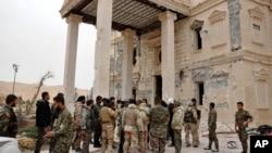 Suriye Haber Ajansı'nın geçtiği bu fotoğrafta, Suriye ordusu askerleri Palmira antik kentinde tahrip olmuş saray önünde bekliyor