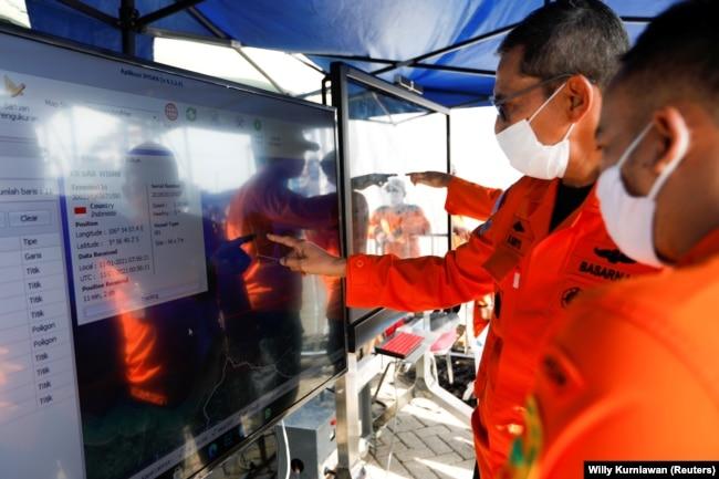 Para petugas tim SAR memperhatikan peta lokasi jatuhnya pesawat Sriwijaya Air SJ 182 di posko di Pelabuhan Tanjung Priok, di Jakarta, Senin, 11 Januari 2021. (Foto: Willy Kurniawan/Reuters)