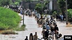 Warga Pakistan dengan membawa barang seadanya mengungsi dari kawasan banjir di Pakistan barat laut.
