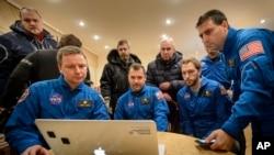 Miembros de la NASA y del equipo ruso que no pudieron viajar debido al clima al lugar del aterrizaje observan el descenso en vivo por computadora.