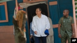 U.N. Secretary-General Ban Ki-moon walks out after visiting the house of a cholera victim during the launching of sanitation campaign in Hinche, Haiti, July 14, 2014.