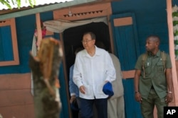 FILE - U.N. Secretary-General Ban Ki-moon walks out after visiting the house of a cholera victim during the launching of sanitation campaign in Hinche, Haiti, July 14, 2014.