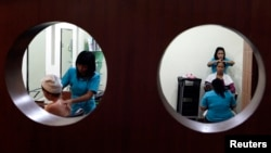 Women receive a massage treatment in a beauty salon in Jakarta January 21, 2009. REUTERS/Beawiharta (INDONESIA) - RTR23OZ1