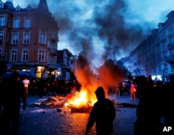 Protesters gather between fires on a street during a protest against the G-20 summit in Hamburg, Germany, July 7, 2017.