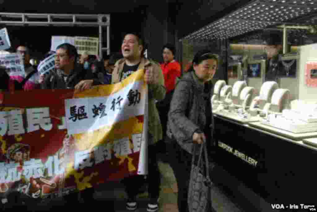 A female tourist from mainland China (right) tries to avoid the protesters. (Iris Tong, VOA)