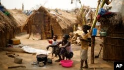 FILE - Families living in a refugee camp prepare food in Kaga-Bandoro, Central African Republic, Tuesday Feb. 16, 2016.