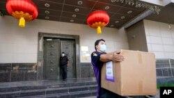 资料照片:一名联邦快递雇员从被美国下令关闭的中国驻休斯顿领事馆搬走一个纸箱。(2020年7月23日)
