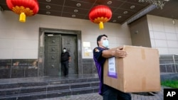 A FedEx employee removes a box from the Chinese Consulate Thursday, July 23, 2020, in Houston.