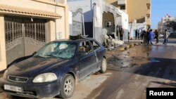 Civilians and security personnel stand at the scene of an explosion at a police station in the Libyan capital Tripoli, March 12, 2015.