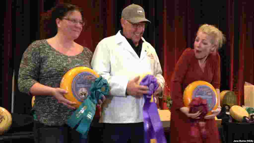 Richard Guggiesberg (center) cradles his champion Baby Swiss cheese. Marieke Penterman (right), whose cheeses placed second and third in the competition, and general manager of her company, Kim Raybuck, also pose on the winners podium, in Green Bay, Wis.,