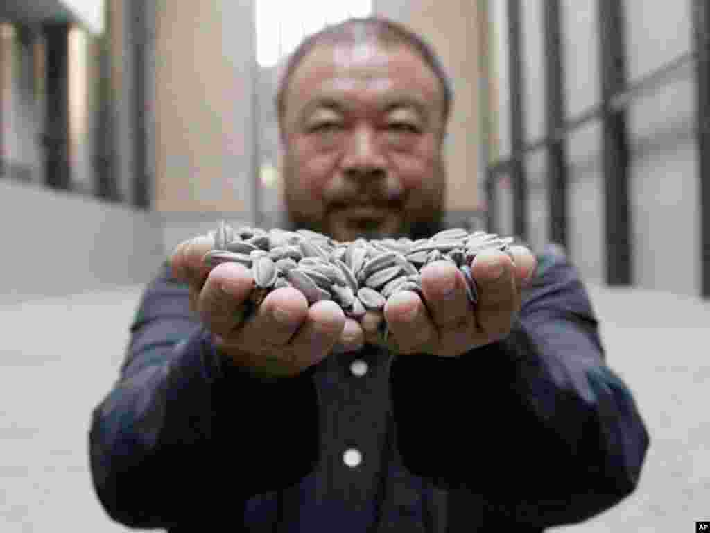 Chinese artist Ai Weiwei was named Most Powerful Artist by ArtReview magazine. He poses for a photograph with his new installation entitled 'Sunflower Seeds', at its unveiling in the Turbine Hall at the Tate Modern gallery, in London October 11, 2010.
