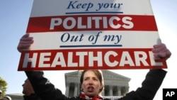 """反對醫療改革的人士3 月27日在華盛頓的聯邦法院門外高舉標語牌""""你的政治不要插手我的醫保""""抗議。"""