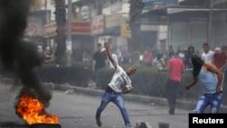 Manifestants palestiniens lancant des pierres sur les soldats israéliens lors d'affrontements dans la ville d'Hébron en Cisjordanie, 23 octobre 2015. (Reuters photo)