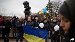 Người dân Ukraina đứng trước tượng nhà thơ Ukraina Taras Shevchenko-biểu tượng quốc gia-đem theo cờ Ukraina trong một cuộc tụ họp phản đối việc chia cắt đất nước, Simferopol, Ukraine, 7/3/2014.