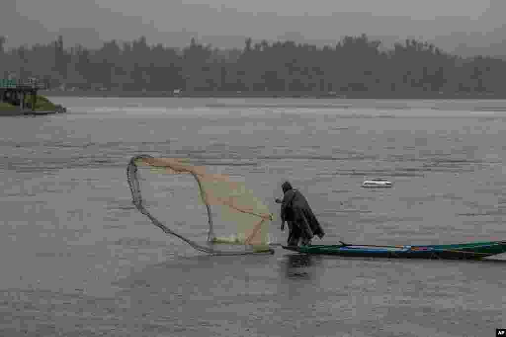 A Kashmiri fisherman throws his net into the water as it rains at the Dal Lake in Srinagar, Indian-controlled Kashmir.