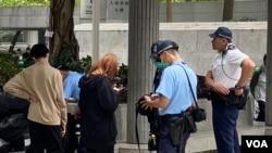 因應網民發起3月2日下午在灣仔稅務大樓靜坐抗議,大批警員在場戒備並截查年輕人。(美國之音 湯惠芸拍攝)