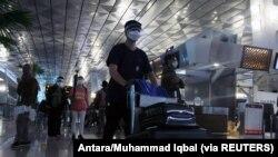 Penumpang yang memakai masker pelindung wajah berjalan di Bandara Soekarno-Hatta di tengah pandemi Covid-19, di Tangerang, 23 Desember 2020. (Foto: Antara/Muhammad Iqbal via Reuters)