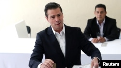 El presidente de México, Enrique Peña Nieto vota en el centro donde está empadronado en Ciudad de México, el 1 de julio de 2018. México elige este día presidente, legisladores y otros altos funcionarios en una histórica votación.