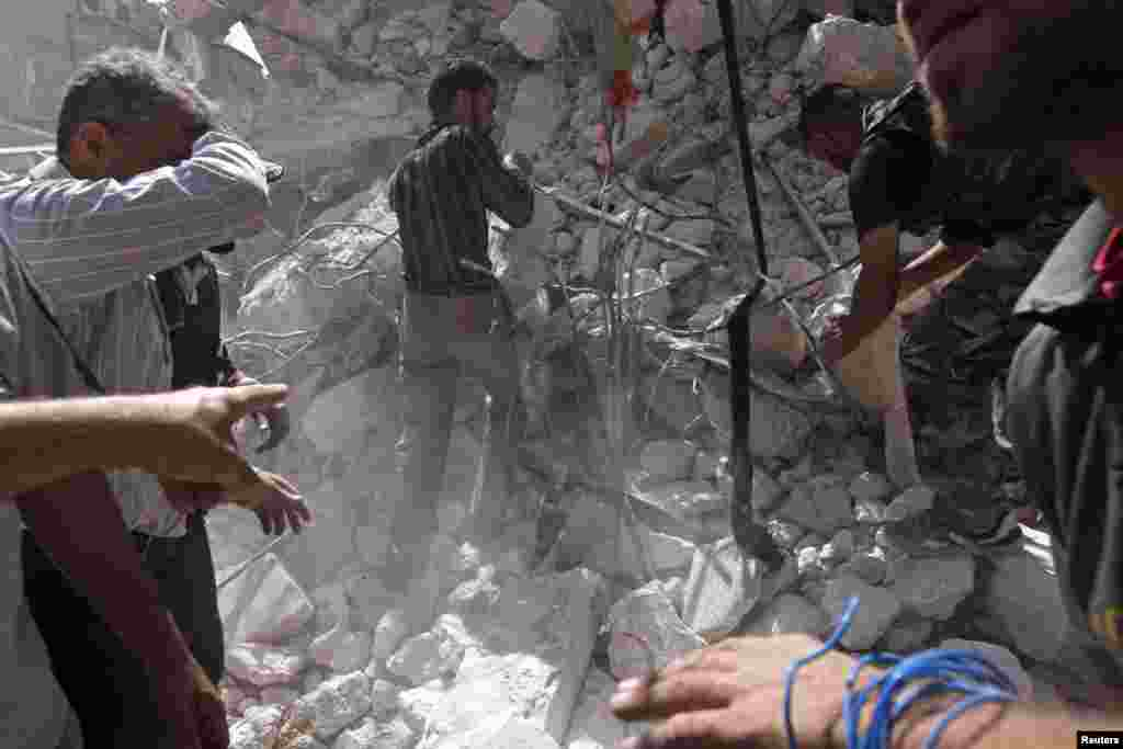 Mülki vətəndaşlar və Suriya Azadlıq ordusunun əsgərləri Hələbdə dağılmış binanın altından cəsədləri çıxarır